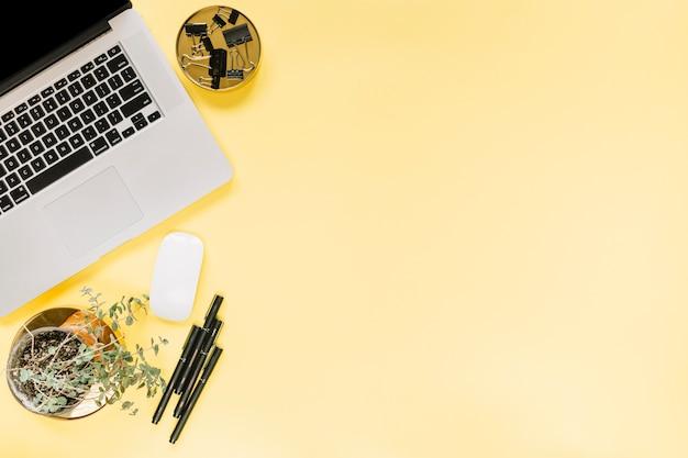 Um laptop aberto; rato com clipes de papel de bulldog e canetas de feltro no fundo amarelo Foto gratuita