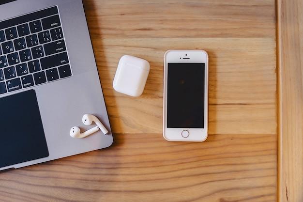 Um laptop, um telefone e um fone de ouvido sem fio em uma mesa de madeira Foto Premium