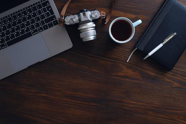 Um laptop, uma xícara de chá, uma câmera e um notebook mentem sobre uma mesa de madeira escura. o local de trabalho de um fotógrafo ou freelancer. copyspace Foto Premium