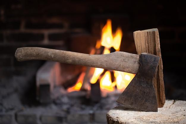 Um machado preso em um toco de madeira perto de uma lareira em chamas. o conceito de conforto e relaxamento na aldeia. Foto gratuita