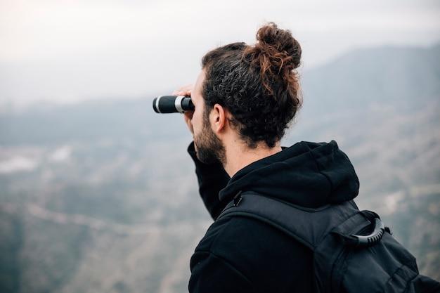 Um, macho, hiker, com, seu, mochila, olhar, vista montanha, através, binocular Foto gratuita