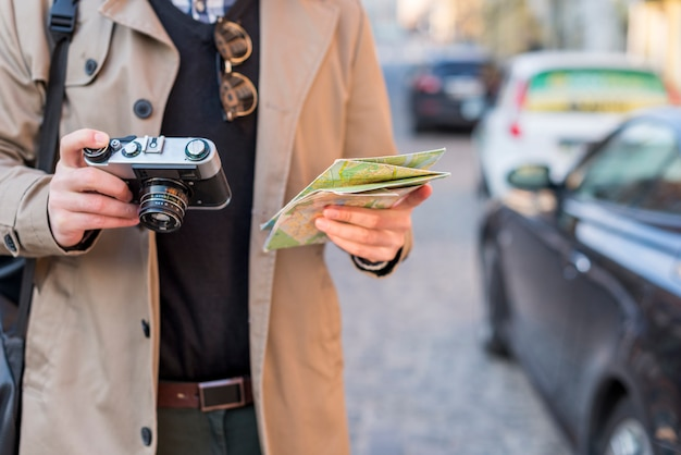 Um, macho, viajante, segurando, mapa, e, vindima, câmera, em, mão Foto gratuita
