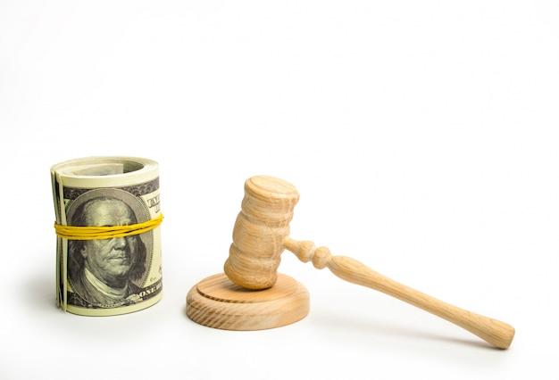 Um martelo de madeira do juiz e um pacote de dólares empacotado em um fundo branco. Foto Premium