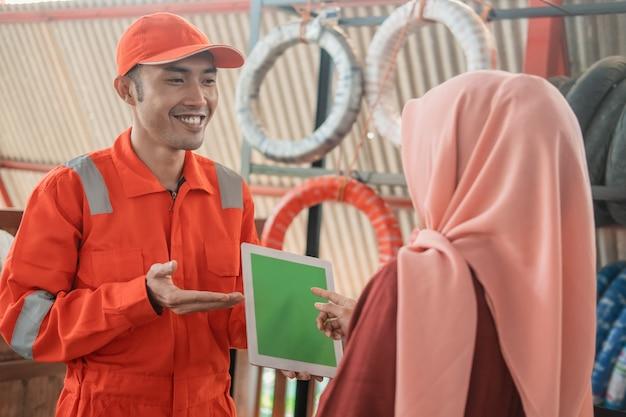 Um mecânico em um wearpack usando um tablet digital com uma cliente usando um hijab contra um suporte de pneus Foto Premium