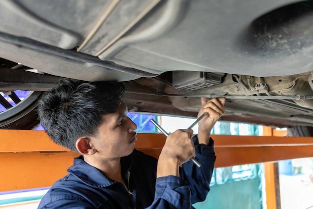 Um mecânico está consertando o motor no elevador do carro. usando ferramentas de chave de reparo de carro na garagem. conceito de carro de serviço. Foto Premium
