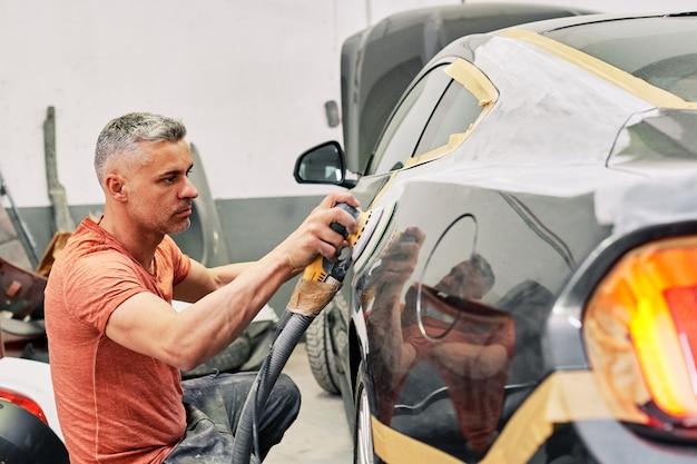 Um mecânico polir um carro esporte Foto Premium
