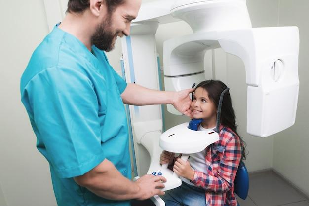 Um médico faz um raio-x da mandíbula da menina. Foto Premium