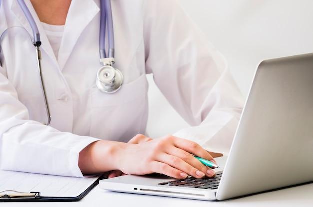 Um, médico feminino, com, estetoscópio, ao redor, dela, pescoço, usando computador portátil, escrivaninha Foto gratuita