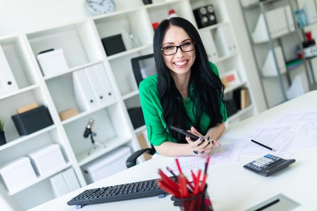 Um, menina jovem, com, óculos, em, escritório, segura, um, telefone, em, dela, mãos, e, sorrisos Foto Premium