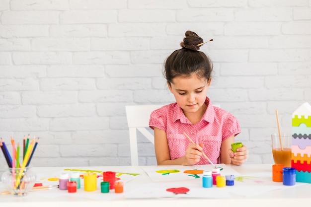 Um, menina, quadro, com, aquarelas, ligado, tabela, contra, branca, parede tijolo Foto gratuita