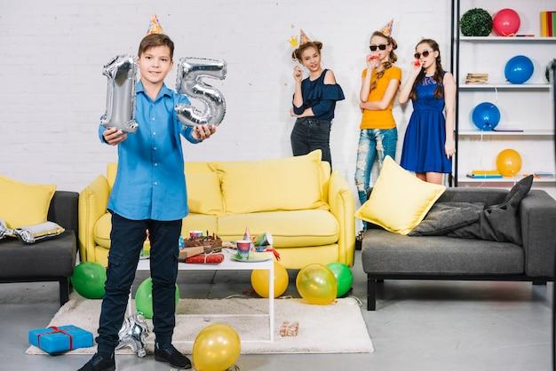 Um, menino aniversário, mostrando, numeral, 15, folha, prata, balões, com, seu, amigos, ficar, em, a, fundo Foto gratuita