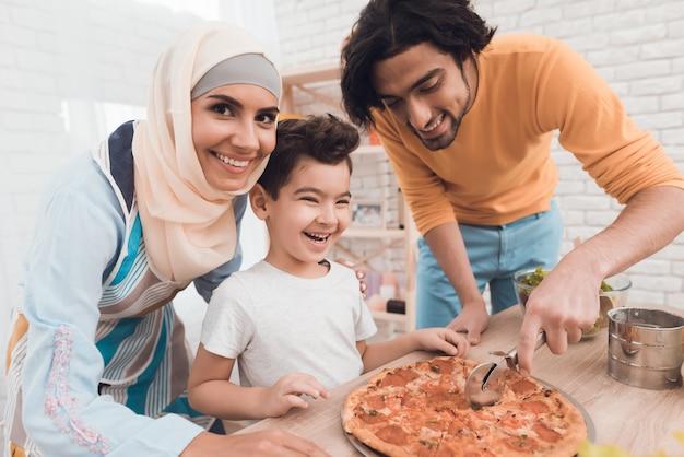 Um menino com seu pai está cortando pizza. Foto Premium