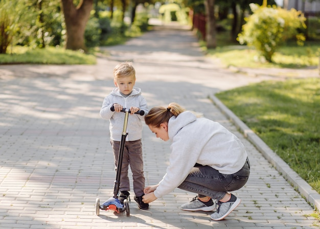 Um menino com sua mãe andando no parque em uma scooter Foto gratuita