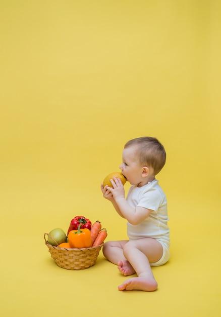 Um menino com uma cesta de legumes e frutas em um espaço amarelo. o bebê se senta de lado e come um limão. orientação vertical. copie o espaço Foto Premium