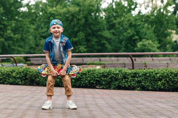 Um menino da cidade pequena e um skate. um jovem está de pé no parque e segurando um skate Foto Premium