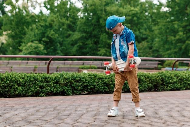 Um menino de cidade pequena e skate. um rapaz está de pé no parque e segurando um skate Foto Premium