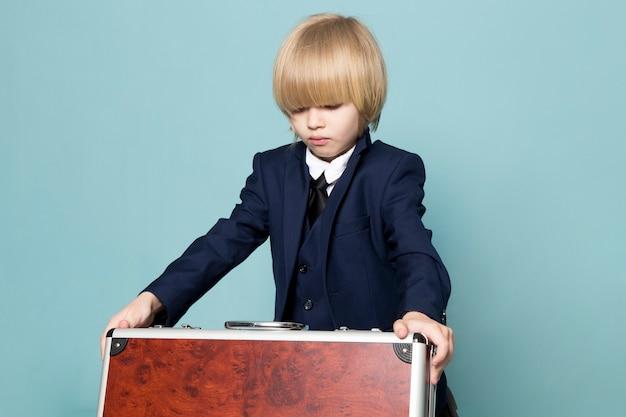 Um menino de negócios bonito vista frontal no terno clássico azul posando segurando segurando a mala marrom-prata negócios trabalho moda Foto gratuita