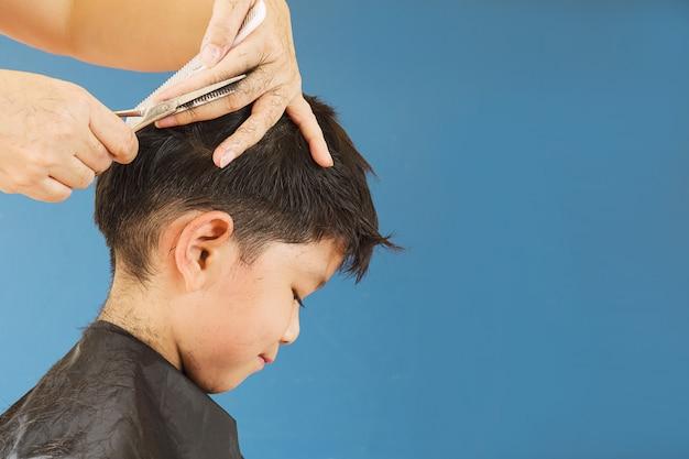 Um menino é cortado o cabelo pelo cabeleireiro Foto gratuita