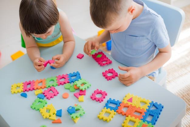 Um menino e uma menina coletar um quebra-cabeça macia na mesa Foto Premium
