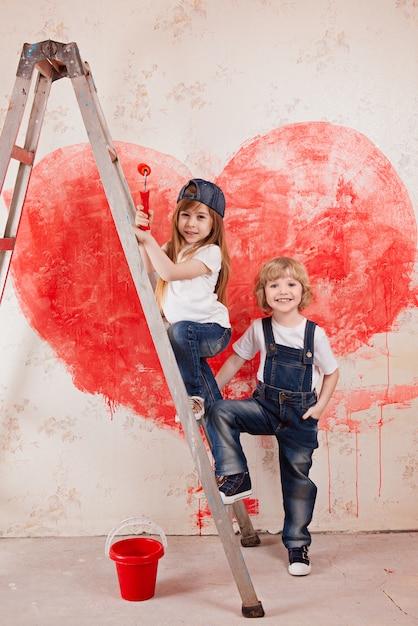 Um menino e uma menina de jeans e uma camiseta branca, com um pincel e um carrinho de balde em uma escada pintar a parede Foto Premium
