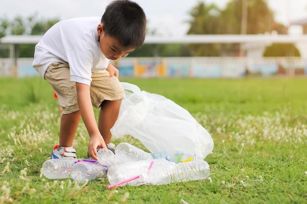 Um menino é voluntário para limpar o chão do campo. ele pegou muitas garrafas de plástico e palha no chão. Foto Premium