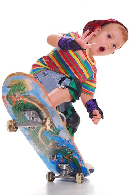 Um menino em roupas brilhantes em um skate empurra para cima. Foto Premium