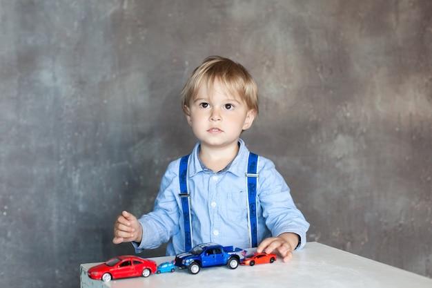 Um menino em uma camisa com suspensórios brinca com carros de brinquedo multi colorido brinquedo. pré-escolar menino brincando com carro de brinquedo em uma mesa em casa ou creche. brinquedos educativos para criança pré-escolar e jardim de infância. Foto Premium