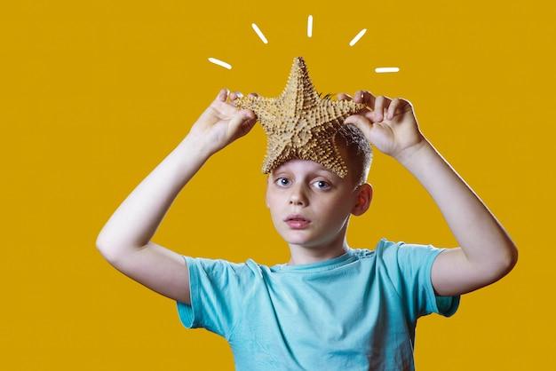 Um menino em uma camiseta leve, segurando uma estrela do mar em um fundo amarelo Foto Premium