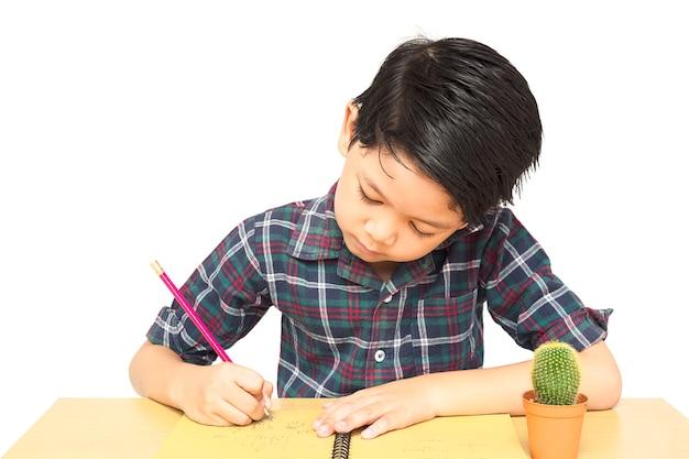 Um menino está curiosamente fazendo lição de casa Foto gratuita