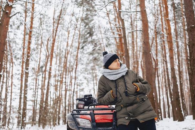 Um menino está de pé perto de uma moto no meio da floresta Foto Premium