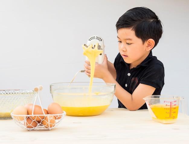 Um menino está fazendo bolo. foto está focada em seu rosto. Foto gratuita