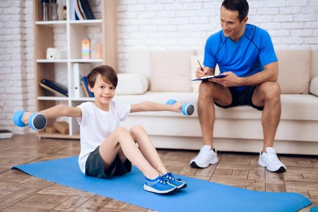 Um menino está fazendo exercícios com halteres no chão. Foto Premium