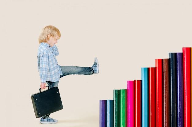 Um menino loiro de cinco anos com uma mochila sobe na escada de lápis. surrealismo, realização de objetivos Foto Premium