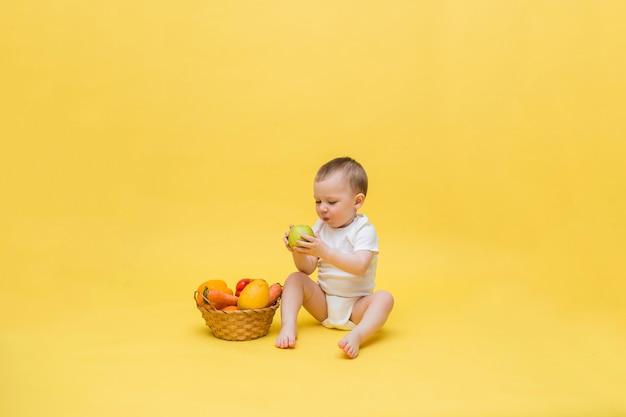 Um menino pequeno com uma cesta de vime com legumes e frutas em um espaço amarelo. o garoto está sentado em uma roupa branca e comendo uma maçã. olhando para o lado. Foto Premium