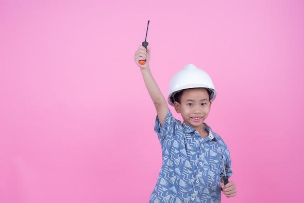 Um menino que fez um gesto de suas mãos usando um capacete em um fundo rosa. Foto gratuita