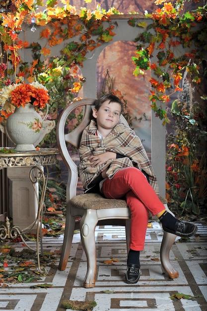 Um menino se senta em uma cadeira com um cobertor Foto Premium