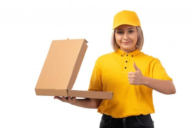 Um mensageiro feminino vista frontal na camisa amarela boné amarelo jeans preto segurando a caixa de pizza e sorrindo em branco Foto gratuita
