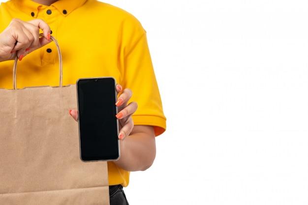 Um mensageiro feminino vista frontal na tampa amarela camisa amarela e calça jeans preta, segurando o pacote com comida e smartphone em branco Foto gratuita