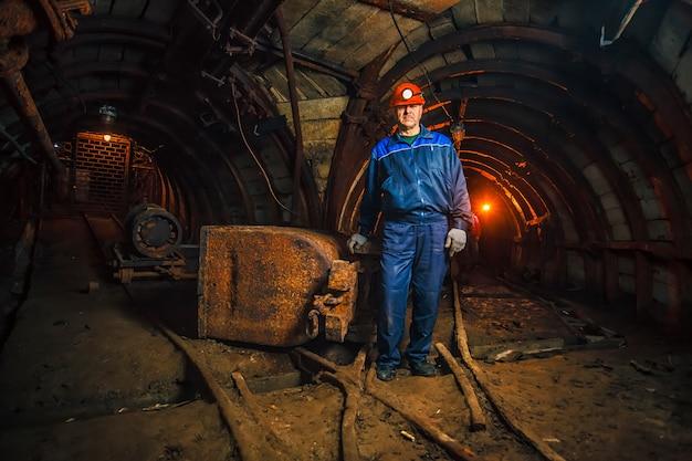 Um mineiro em uma mina de carvão está perto de um carrinho. copie o espaço. Foto Premium