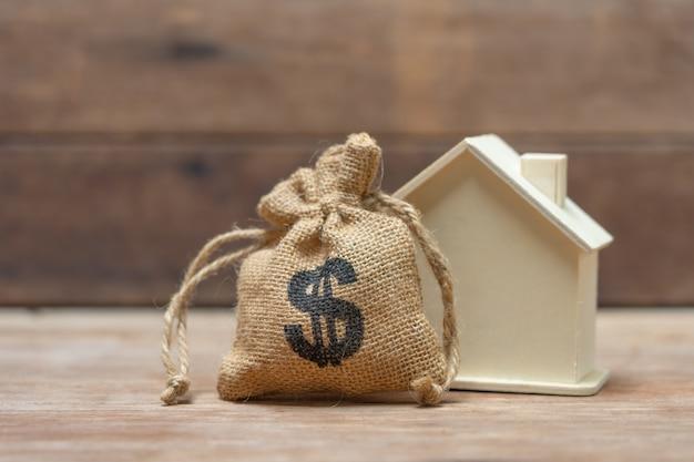 Um modelo de casa modelo é colocado em uma pilha de moedas Foto Premium