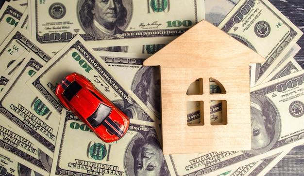 Um modelo e um carro de madeira da casa com dólares americanos. compra e venda ou seguro de carro. Foto Premium