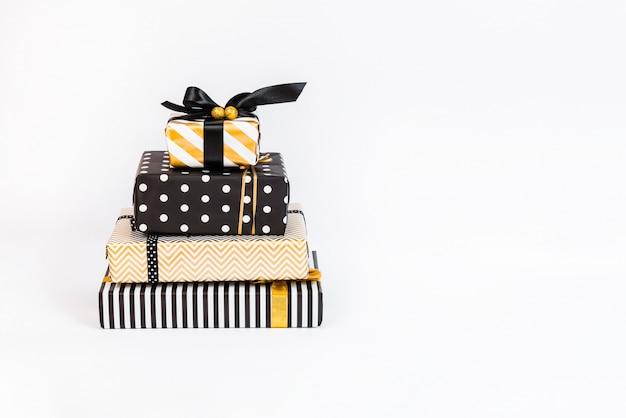 Um monte de caixas de presente em várias cores preto, branco e dourado Foto Premium