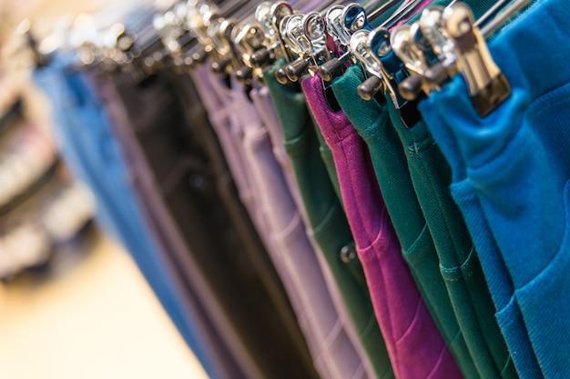 Um monte de calças jeans coloridas penduradas em cabides em uma loja de roupas Foto Premium