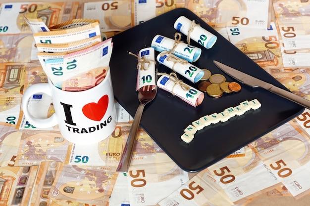 Um monte de notas de dinheiro dinero em um prato com uma faca, um garfo e uma xícara com placa de troca de amor Foto gratuita