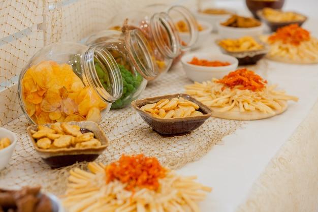 Um monte de salgadinhos em uma mesa, muitos queijos e bolachas em cima da mesa com salgadinhos Foto Premium