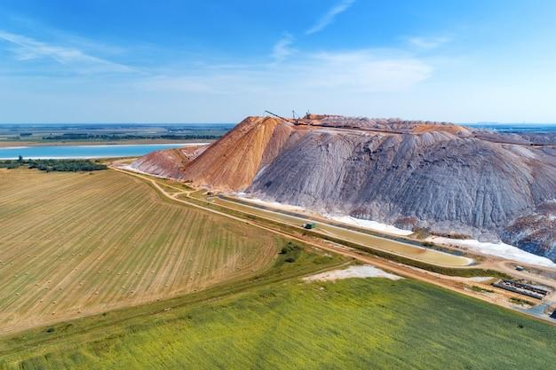 Um monte enorme de sal de potássio. armazenagem de rochas com a ajuda de um espalhador Foto Premium