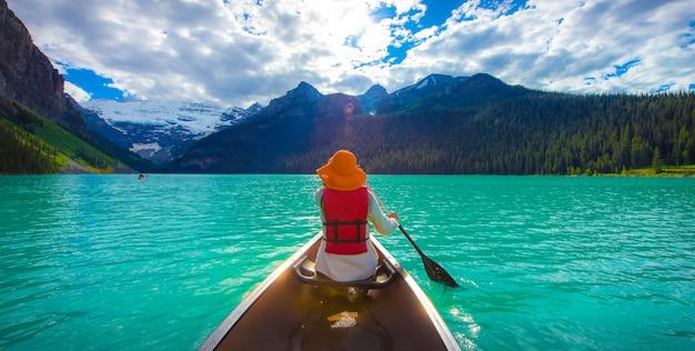 Um, mulher, em, vermelho, casaco vida, canoagem, em, lago louise, com, torquoise, lago, e, bluesky Foto Premium