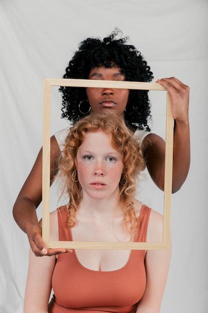 Um, mulher jovem africana, segurando, frame madeira, frente, caucasiano, femininas, contra, cinzento, fundo Foto gratuita