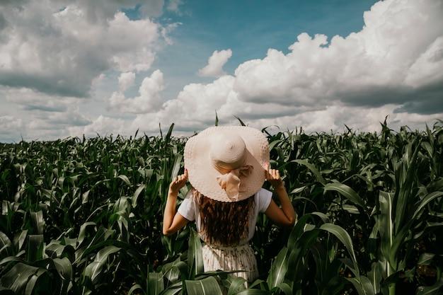 Um, mulher jovem, é, ficar, em, um, jardim tropical, olhar distância, segurando, dela, chapéu, com, dela, mãos Foto Premium