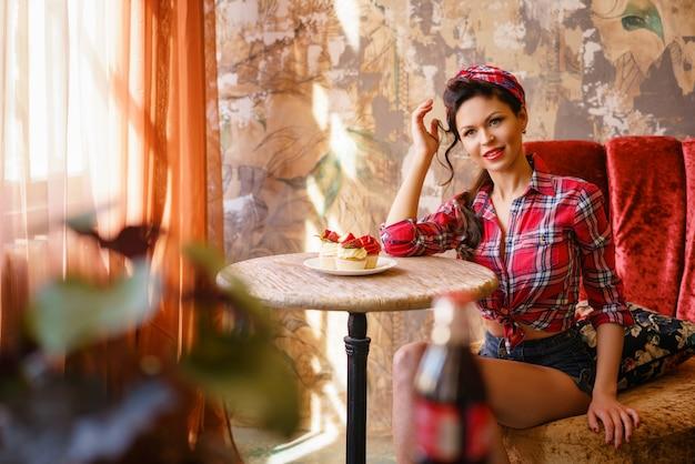 Um, mulher jovem, em, um, café, sentando uma tabela, com, bolos, arquive Foto Premium